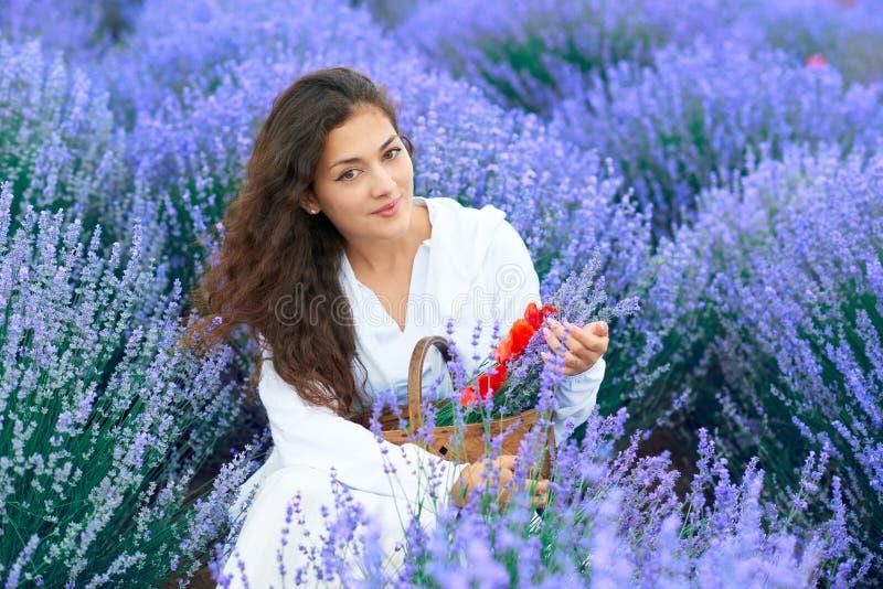 A jovem mulher com papoila est? no campo de flor da alfazema, paisagem bonita do ver?o fotos de stock royalty free