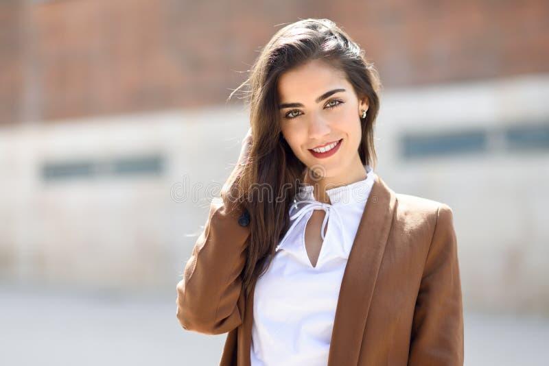 Jovem mulher com parte externa ereta do cabelo agradável do prédio de escritórios fotos de stock