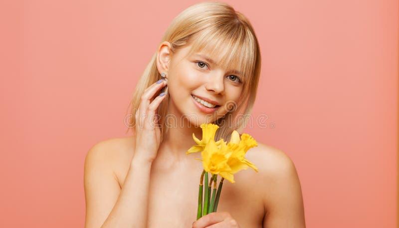 Jovem mulher com pele fresca e os cabelos saudáveis que guardam narciso e sorriso Cosmetologia, beleza e termas foto de stock royalty free