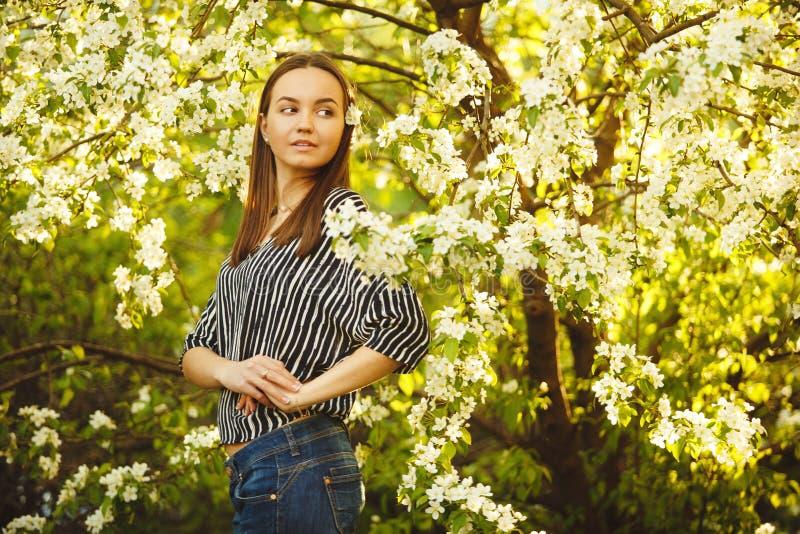 Jovem mulher com pele limpa perto de uma árvore de maçã de florescência Retrato da menina no parque da mola imagens de stock royalty free