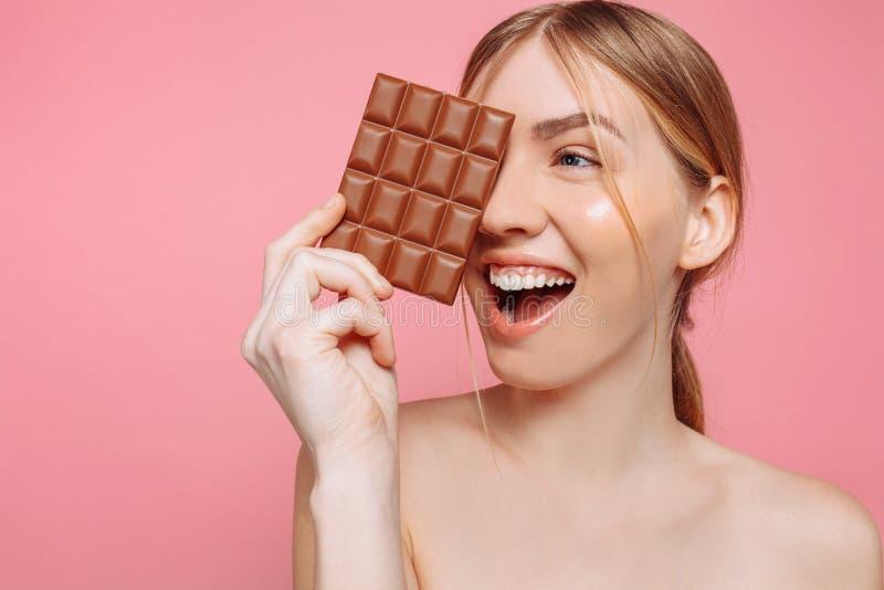 Jovem mulher com a pele limpa que guarda uma barra de chocolate preta em suas mãos, fechando um olho com chocolate em um fundo co imagem de stock