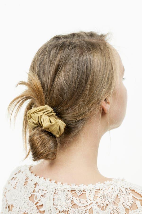 Jovem mulher com penteado desarrumado ocasional do bolo fotografia de stock