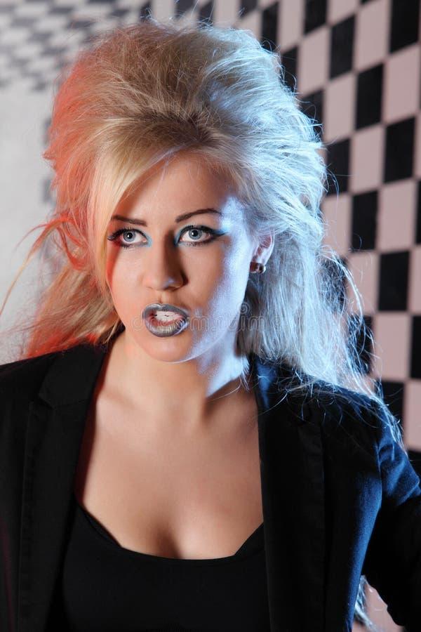 A jovem mulher com penteado e composição incomuns canta no estúdio fotografia de stock