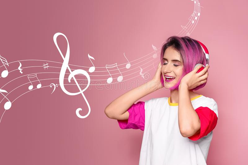 Jovem mulher com penteado na moda que escuta a música imagens de stock royalty free