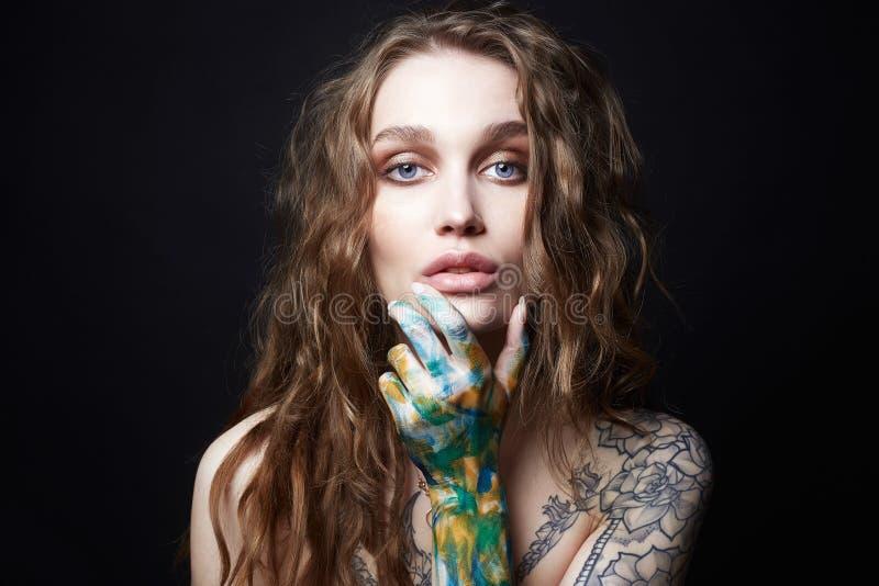 Jovem mulher com pintura da tatuagem e da cor em seu corpo foto de stock royalty free