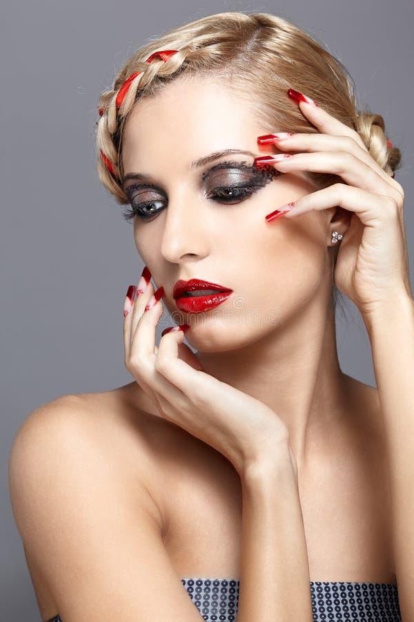 Jovem mulher com pregos vermelhos fotografia de stock royalty free