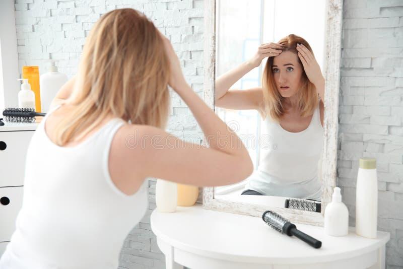 Jovem mulher com problema da queda de cabelo na frente do espelho foto de stock royalty free