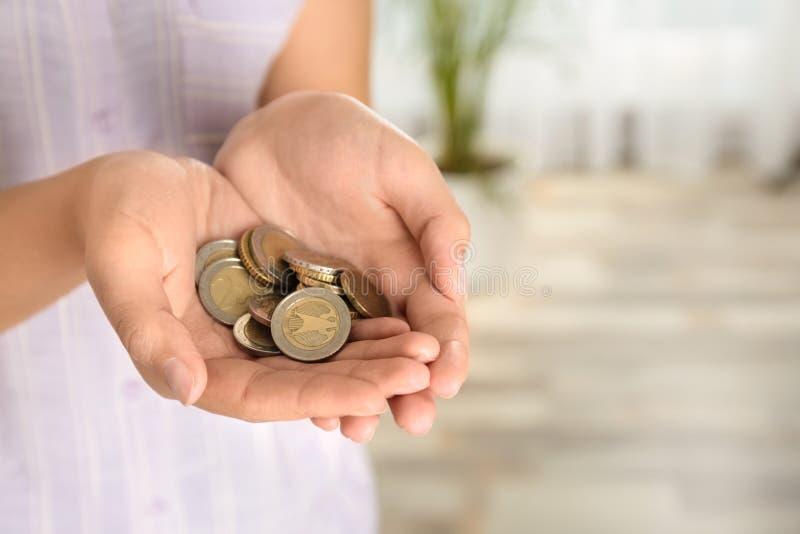 Jovem mulher com punhado das moedas dentro, opinião do close up Espa?o para foto de stock royalty free