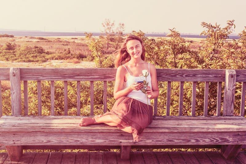 Jovem mulher com a rosa do branco, esperando o fora imagens de stock