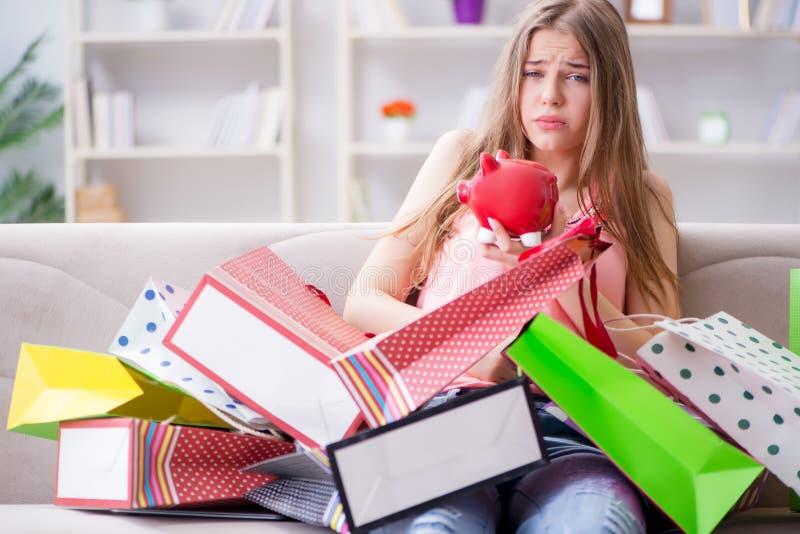 A jovem mulher com sacos de compras dentro dirige no sofá imagens de stock