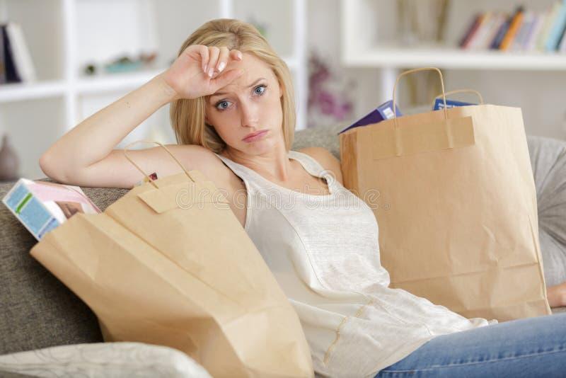 A jovem mulher com sacos de compras dentro dirige no sof? imagem de stock