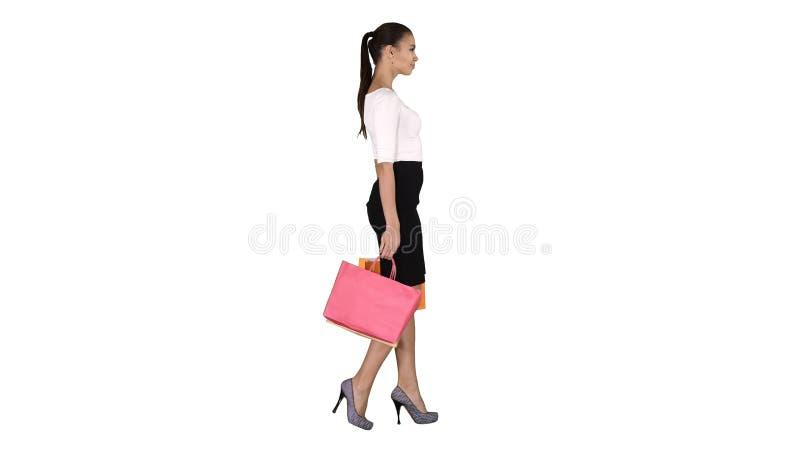 Jovem mulher com sacos de compras que anda para fora da loja no fundo branco foto de stock