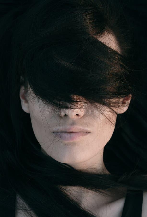 Jovem mulher com seu cabelo através de seus olhos fotos de stock