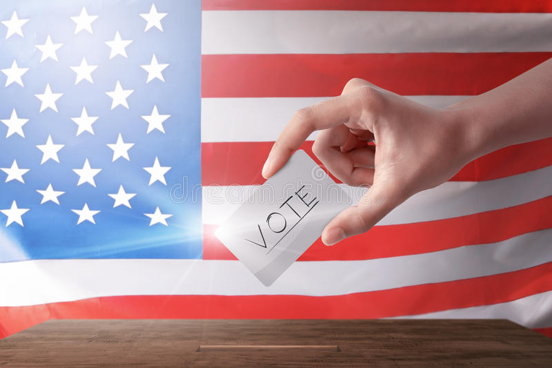 Jovem mulher com seu voto na cabina de voto fotos de stock royalty free