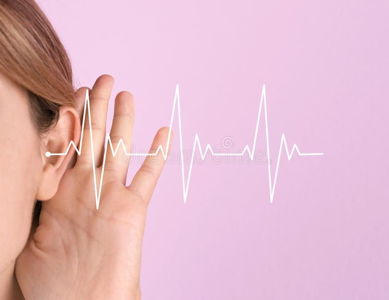 Jovem mulher com sintoma da perda da audição fotografia de stock