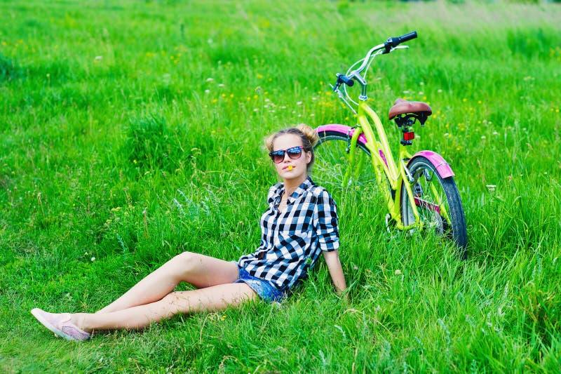 Jovem mulher com sua bicicleta fora foto de stock