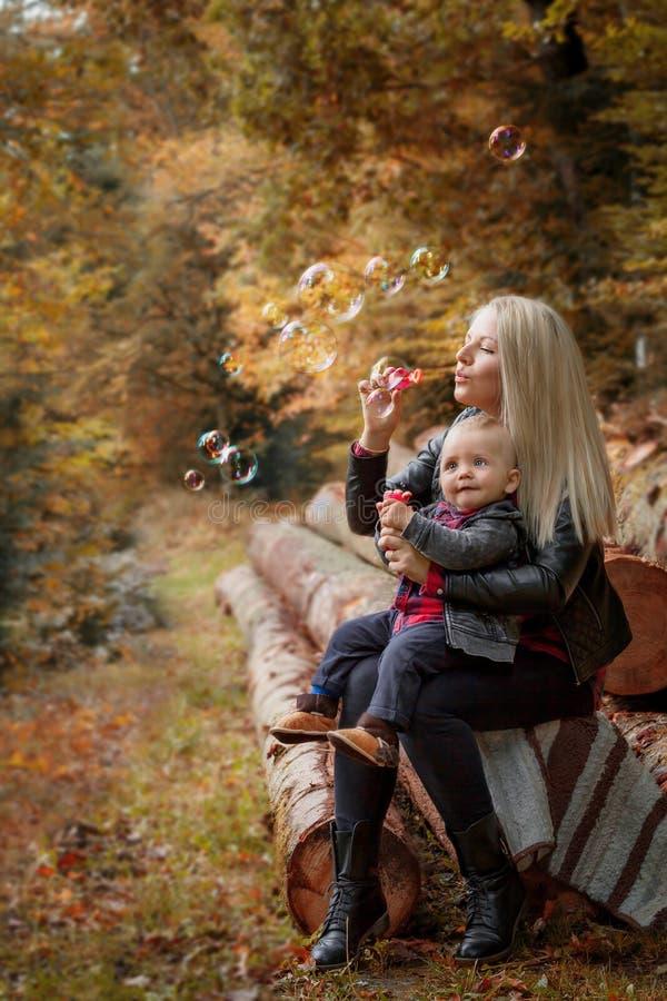 jovem mulher com suas bolhas dos sopros do filho imagens de stock