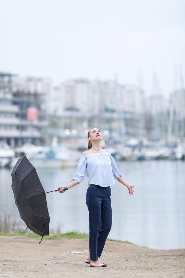 Jovem mulher com suportes de guarda-chuva no litoral e nos olhares acima imagens de stock