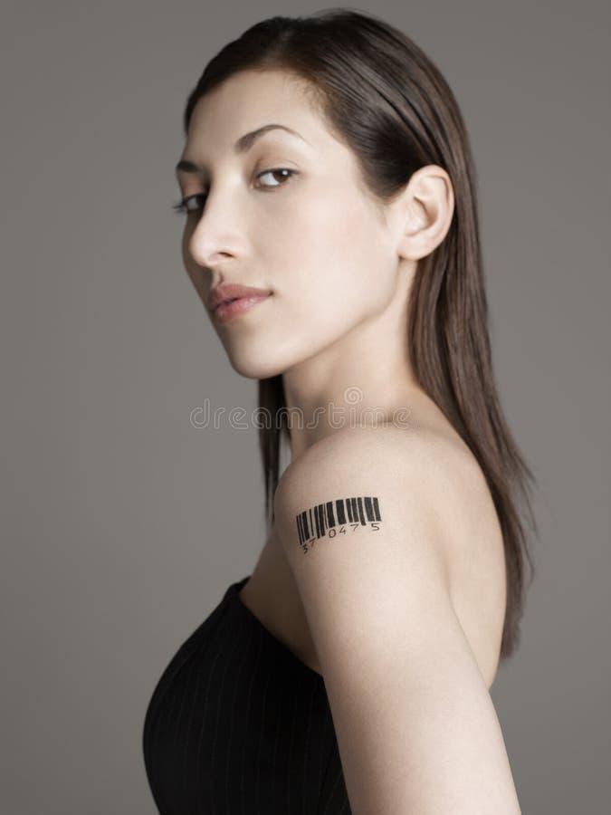 Jovem mulher com tatuagem do código de barras no braço imagem de stock