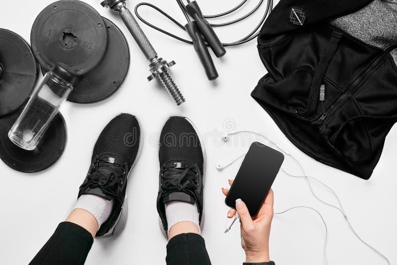 Jovem mulher com telefone celular e equipamento de esporte na opinião superior colocada do fundo plano branco Conceito da aptidão fotografia de stock royalty free