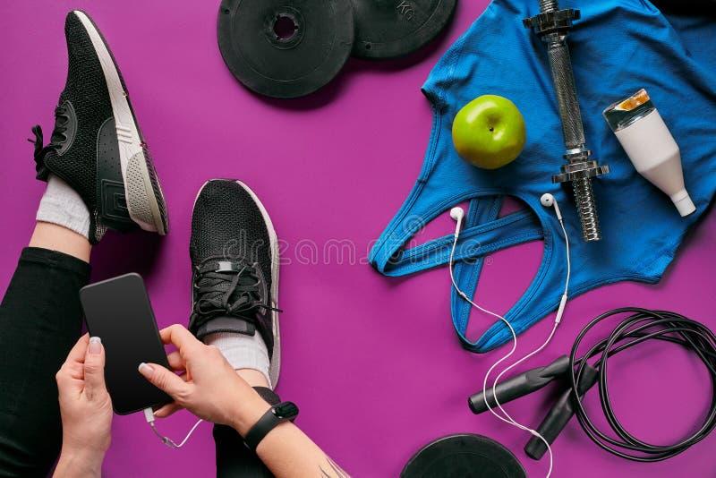 Jovem mulher com telefone celular e equipamento de esporte na opinião superior colocada plano do fundo da cor Conceito da aptidão imagens de stock royalty free
