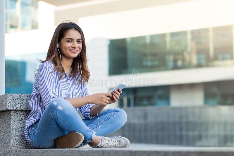 A jovem mulher com telefone que escuta a música, sentando-se relaxou exterior com espaço da cópia imagens de stock