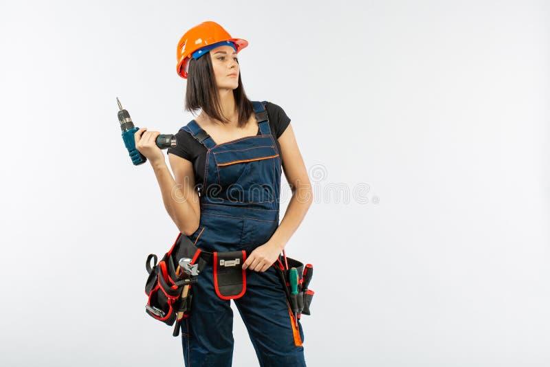 A jovem mulher com toolbelt usando o driil e algumas ferramentas elétricas para ela trabalham em casa Menina que trabalha na remo fotografia de stock royalty free
