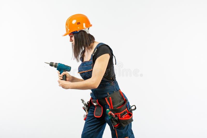 A jovem mulher com toolbelt usando o driil e algumas ferramentas elétricas para ela trabalham em casa Menina que trabalha na remo fotos de stock royalty free