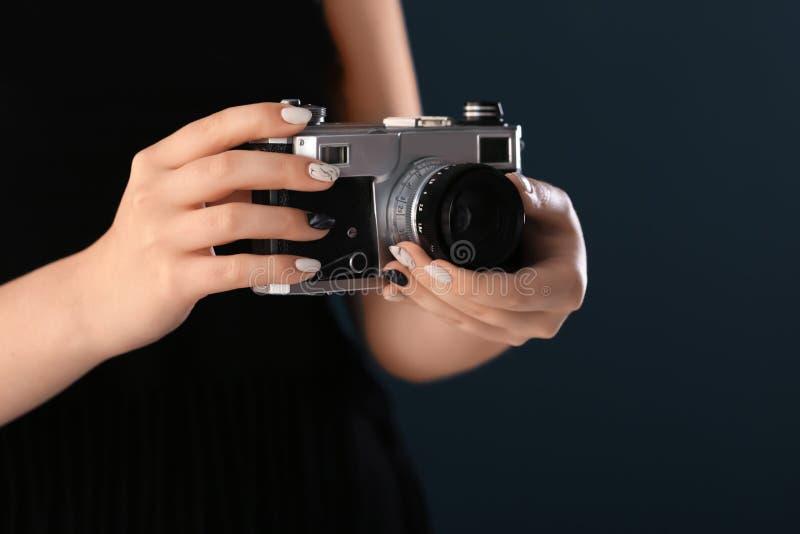 Jovem mulher com tratamento de mãos bonito e câmera retro da foto no fundo escuro, close up fotografia de stock royalty free