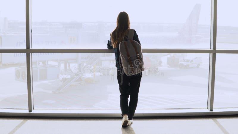 Jovem mulher com a trouxa perto da janela terminal Turista fêmea caucasiano que usa o smartphone na sala de estar do aeroporto Cu foto de stock royalty free