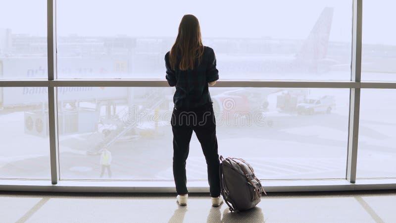 Jovem mulher com a trouxa perto da janela terminal Turista fêmea caucasiano que usa o smartphone na sala de estar do aeroporto Cu fotografia de stock