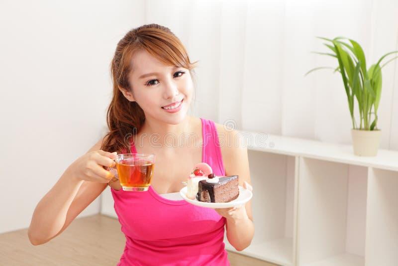 Jovem mulher com um bolo e um chá foto de stock royalty free