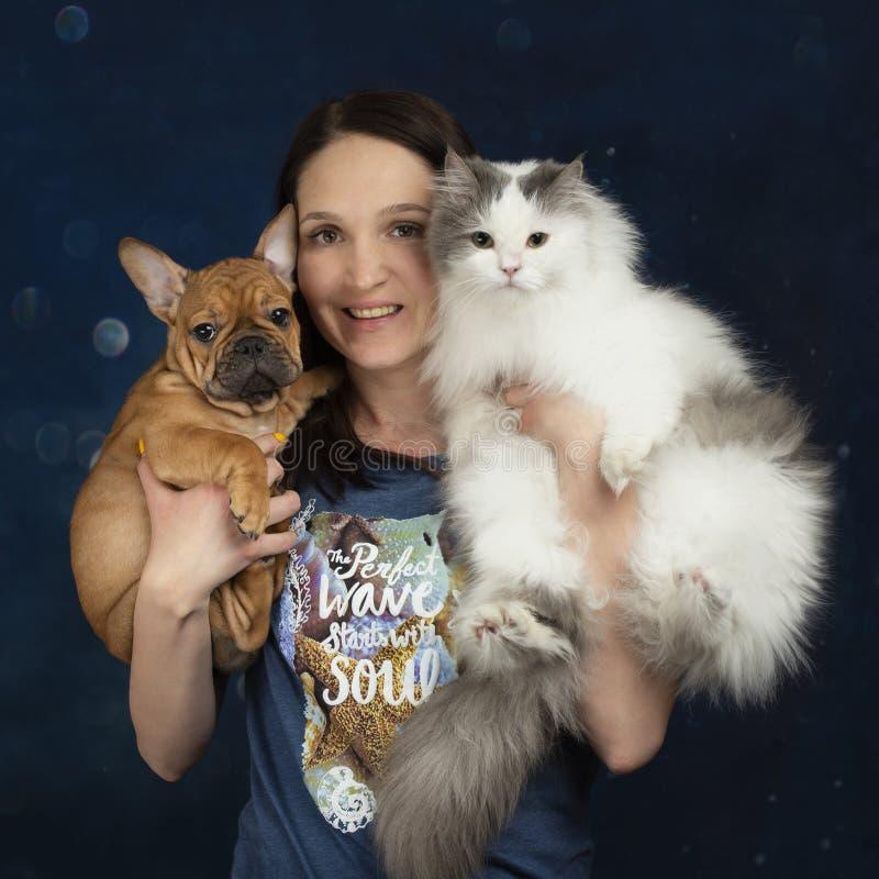 Jovem mulher com um cachorrinho e um gato em seus braços imagens de stock royalty free