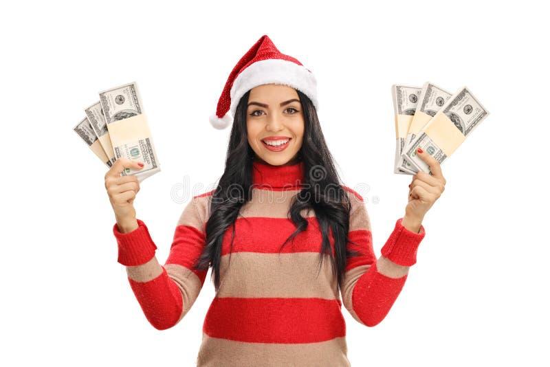 A jovem mulher com um chapéu do Natal com dinheiro empacota foto de stock