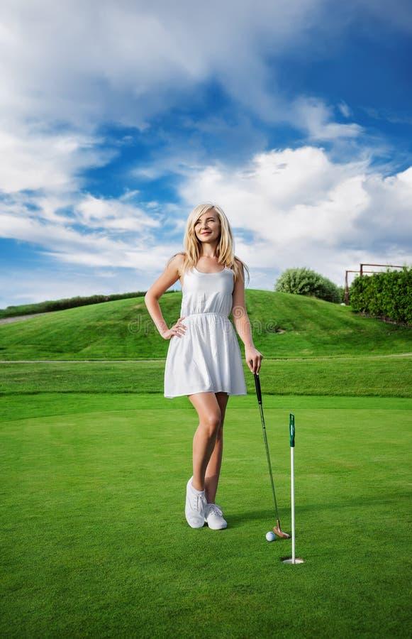 Jovem mulher com um clube de golfe imagem de stock royalty free