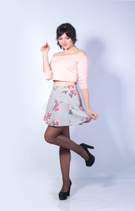 A jovem mulher com um coração em seu mordente em uma mini saia sorri sobre foto de stock