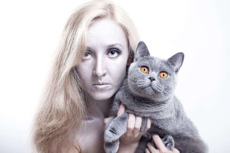 Jovem mulher com um gato britânico cinzento imagens de stock