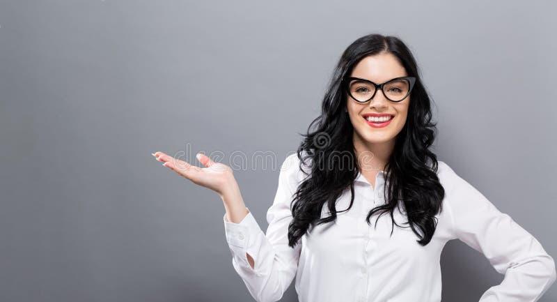 Jovem mulher com um gesto de mão de indicação fotos de stock