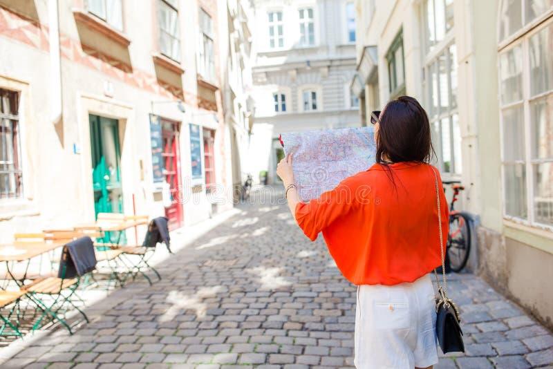 Jovem mulher com um mapa da cidade na cidade Menina do turista do curso com o mapa em Viena fora durante feriados em Europa imagem de stock