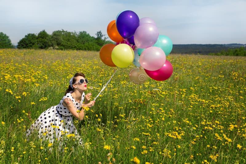 Jovem mulher com um olhar do Pinup, muitos balões e um blowball foto de stock royalty free