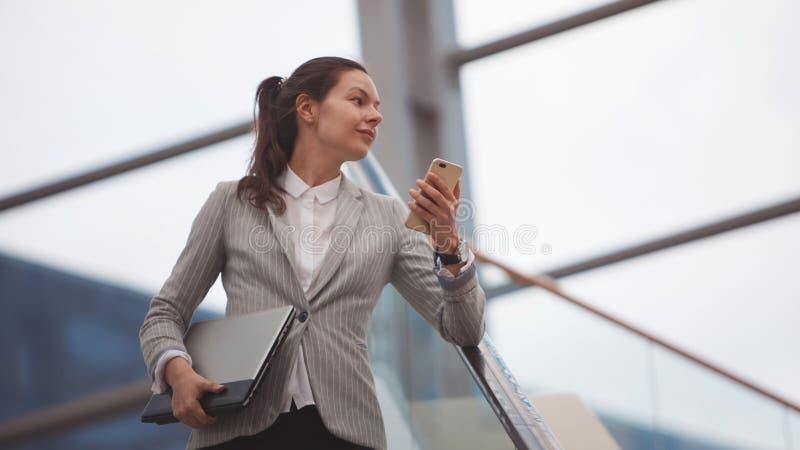 Jovem mulher com um portátil em suas mãos em um centro de negócios, um escritório brilhante moderno Carreira e trabalho imagens de stock
