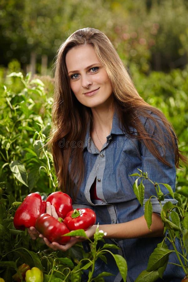 Jovem mulher com um punhado da paprika vermelha fotos de stock royalty free