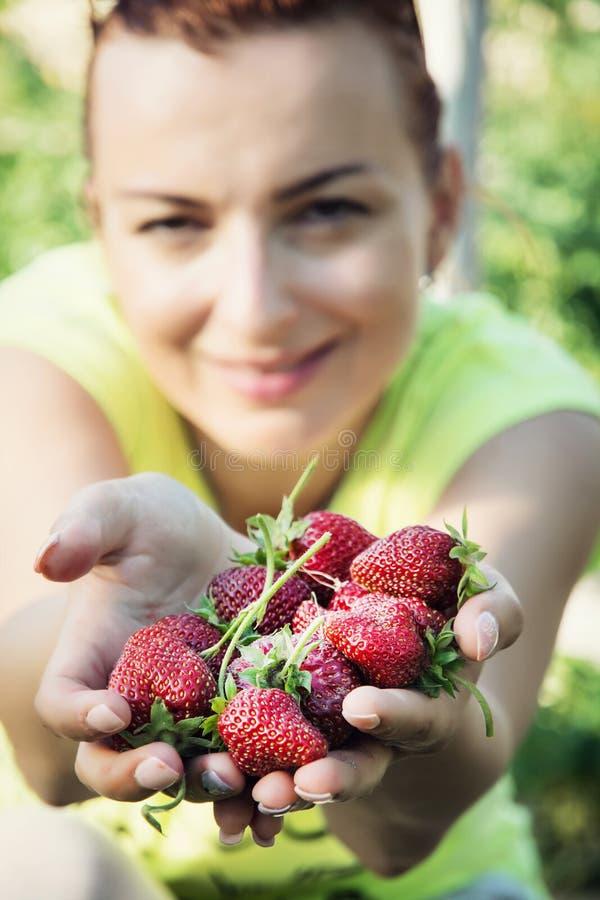 Jovem mulher com um punhado de morangos frescas fotos de stock