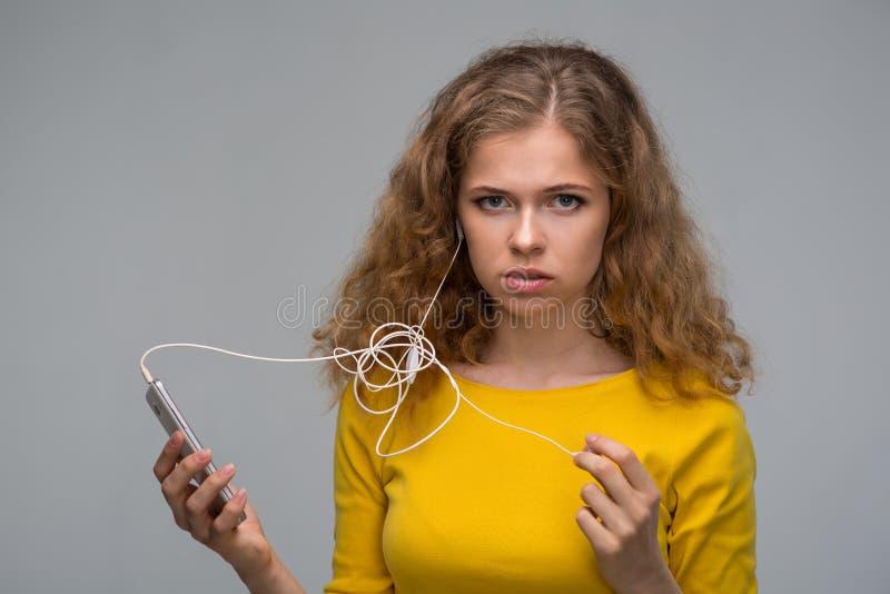 Jovem mulher com um smartphone e os fones de ouvido com um wir tangled imagem de stock royalty free