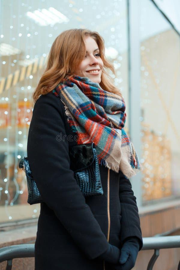 Jovem mulher com um sorriso bonito em um revestimento do inverno em luvas pretas com um lenço de lã da forma com uma bolsa imagens de stock