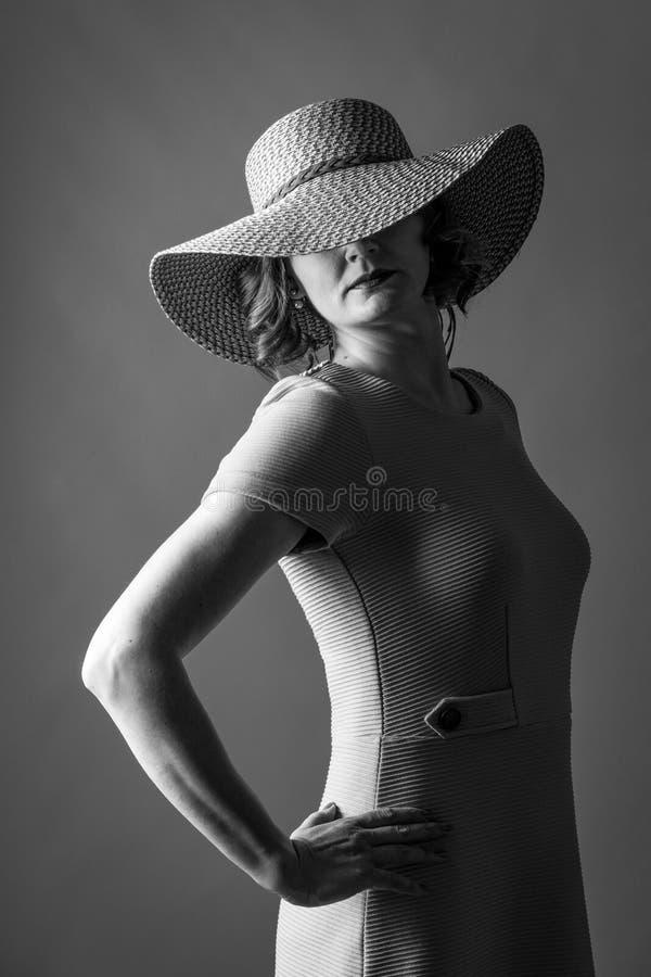 Jovem mulher com um vestido agradável do chapéu e uns bordos vermelhos imagem de stock