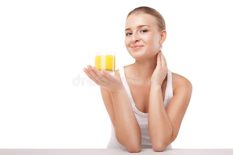 Jovem mulher com um vidro do suco de laranja isolado fotografia de stock