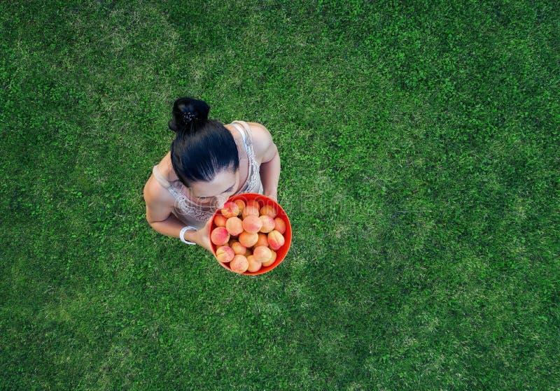 Jovem mulher com uma bandeja de fruto em um fundo da grama verde imagens de stock