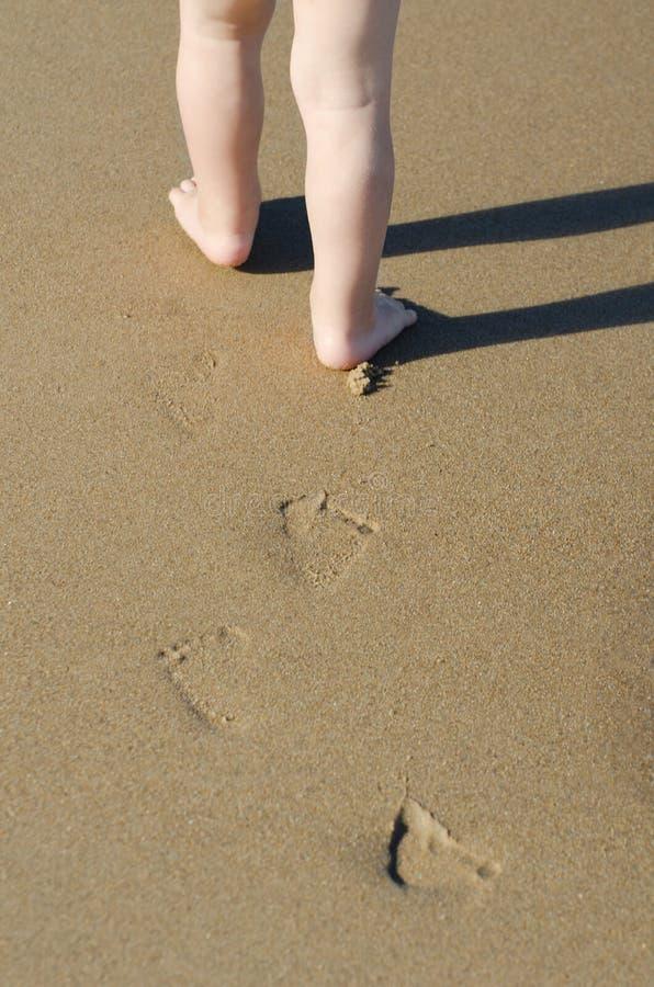 A jovem mulher com uma criança pequena vai ao longo da linha do mar, dia de verão ensolarado fotografia de stock royalty free