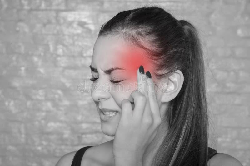Jovem mulher com uma dor de cabeça terrível imagens de stock